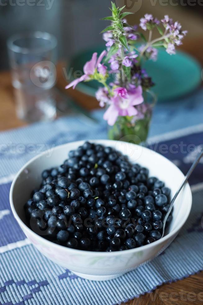Schüssel mit frisch gepflückten Blaubeeren auf dem Tisch foto