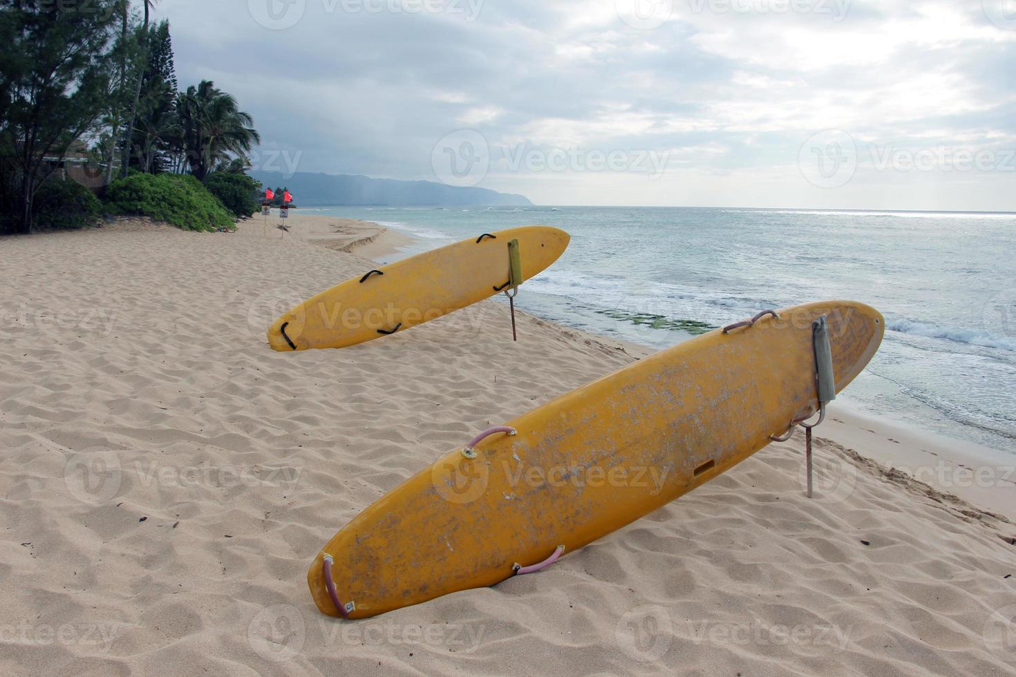 Surfbretter und rote Fahnen am Strand foto