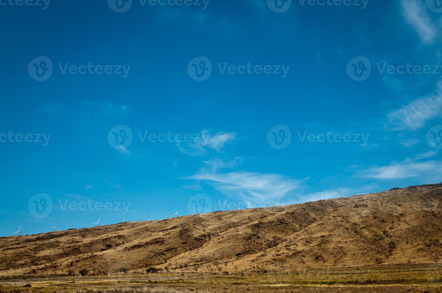 entfernte Windkraftanlagen auf einem trockenen Hügel foto