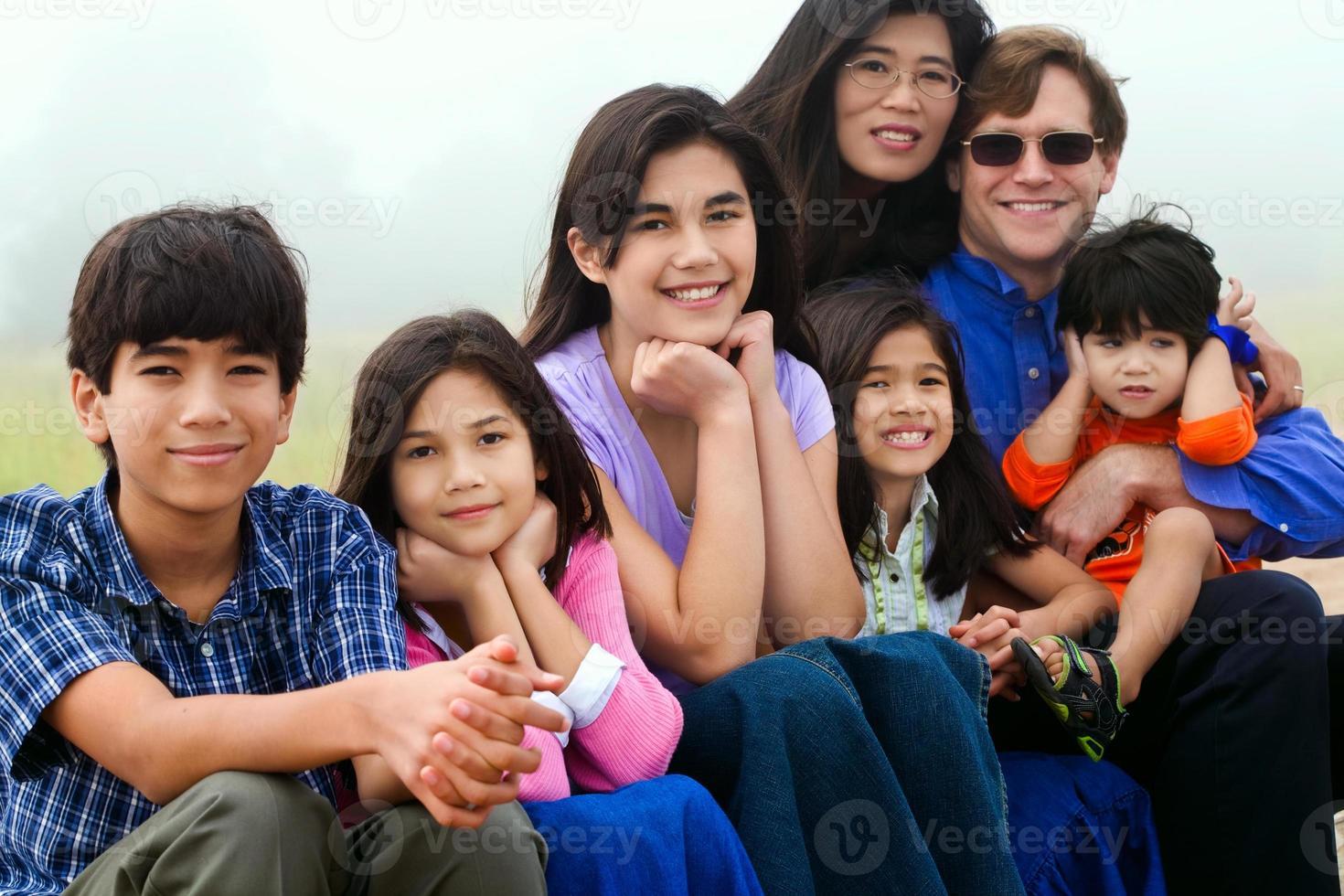 gemischtrassige Familie, die am Strand sitzt foto