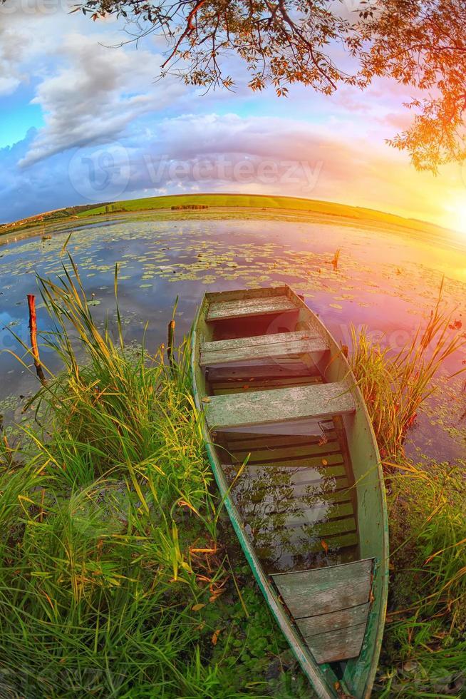 Boot im Schilf auf dem See bei Sonnenuntergang foto
