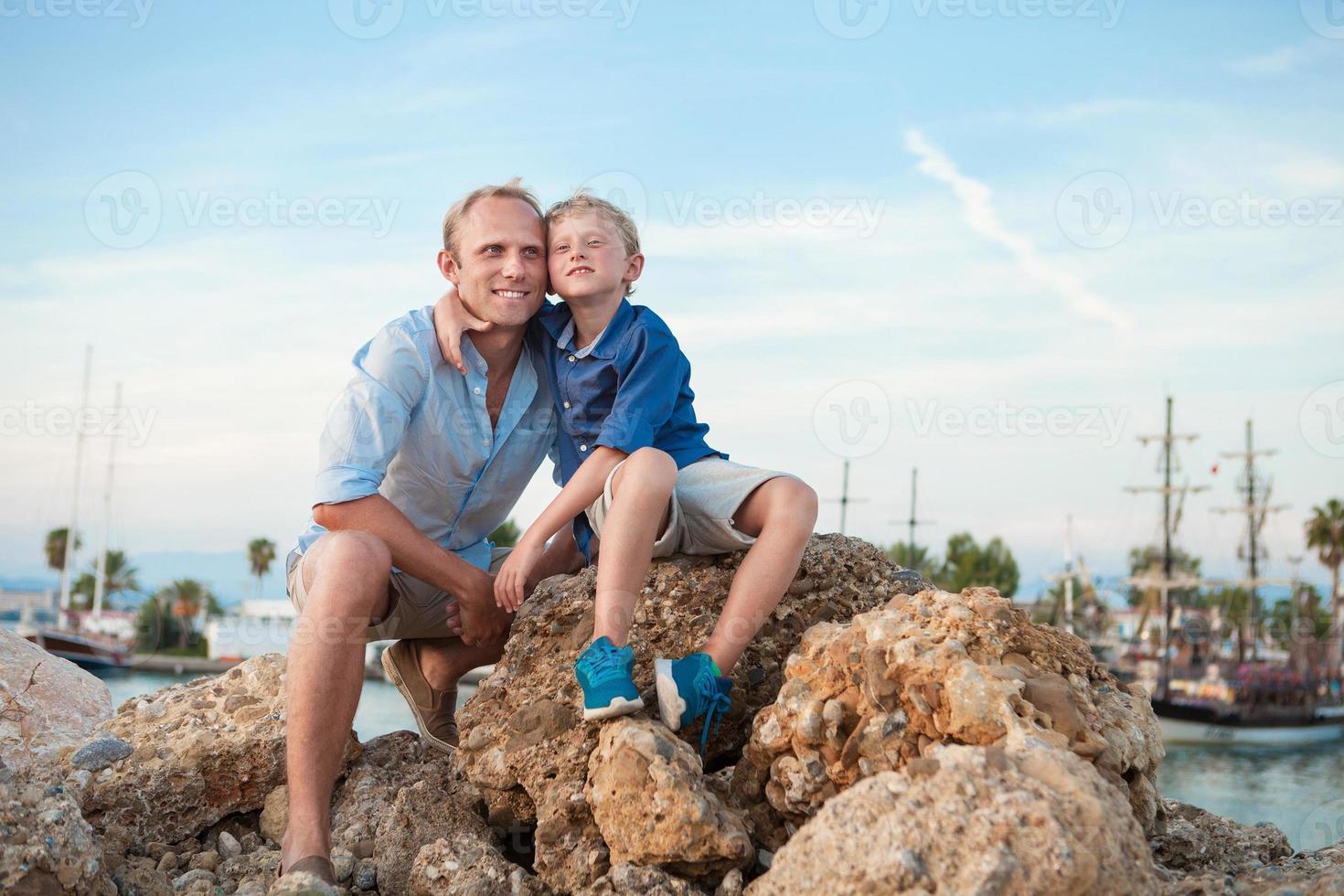 glücklicher Vater und Sohn im Sonnenuntergang Seehafen foto