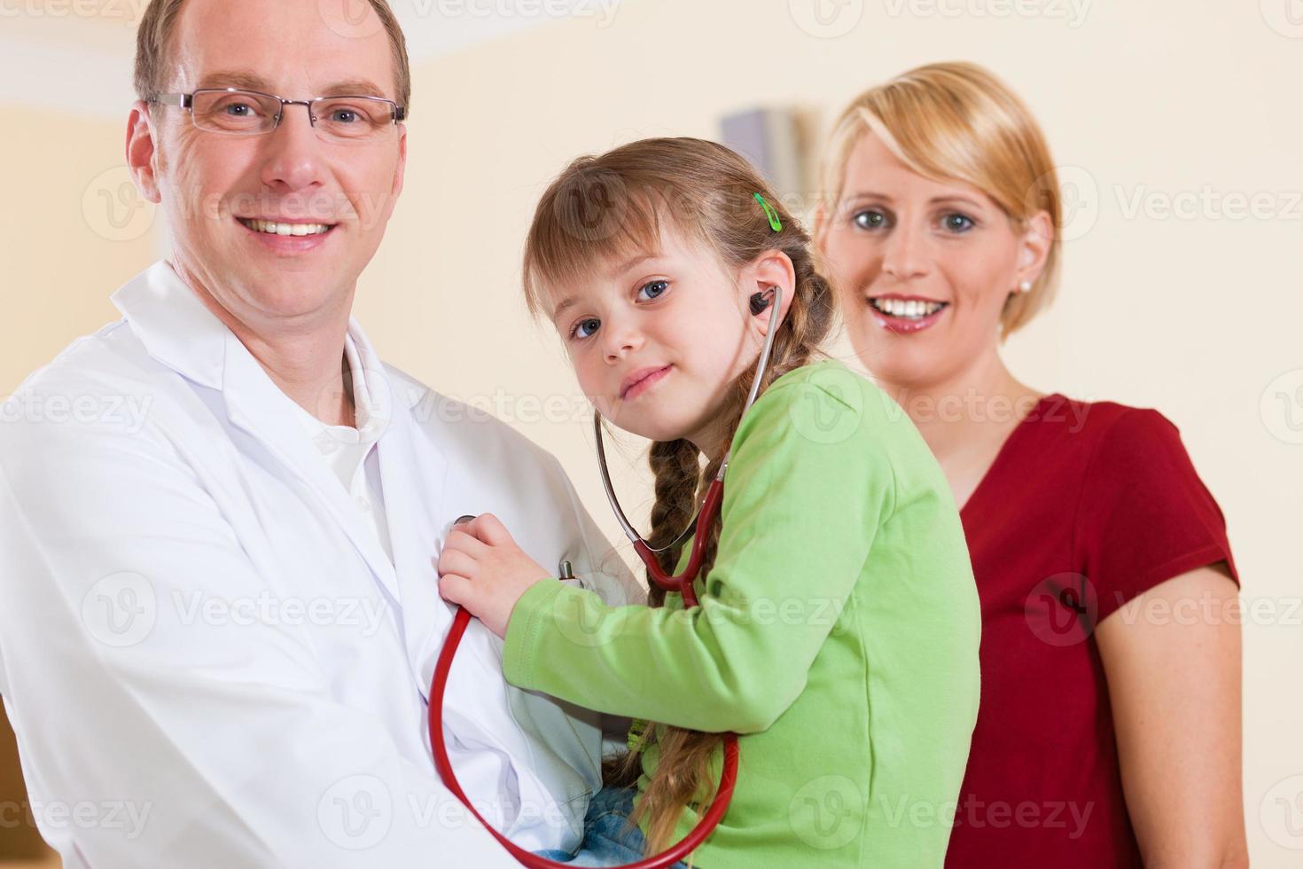 Kinderarzt mit Familie in seiner Praxis foto
