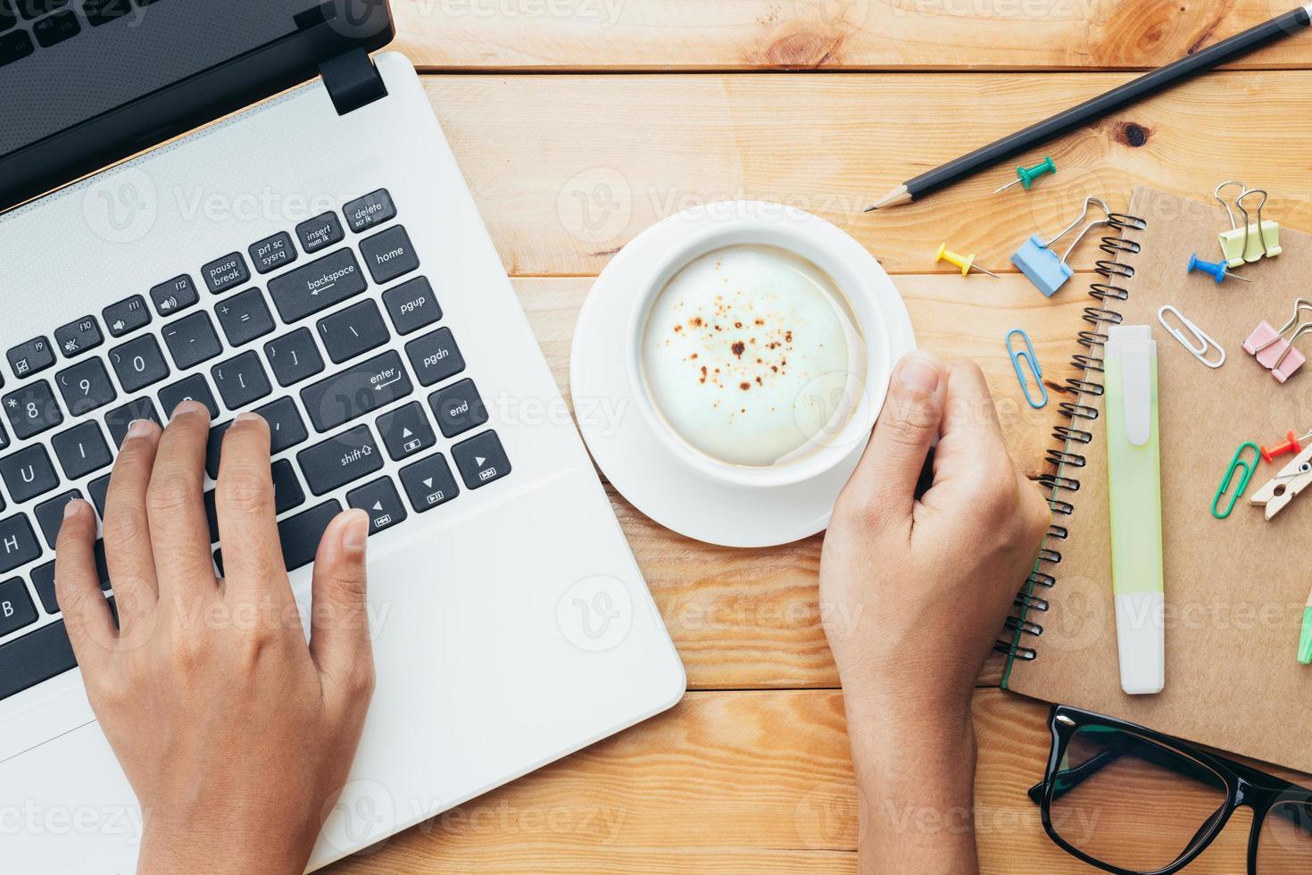Nahaufnahmehand unter Verwendung des Computers und des Haltens des Kaffees am Arbeitsplatz foto
