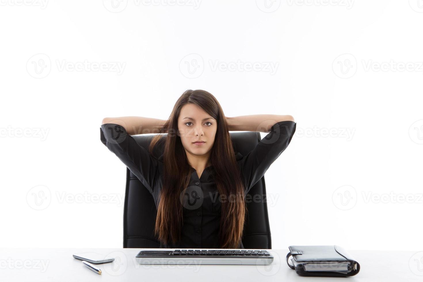 Geschäftsfrau sitzt an ihrem Schreibtisch foto