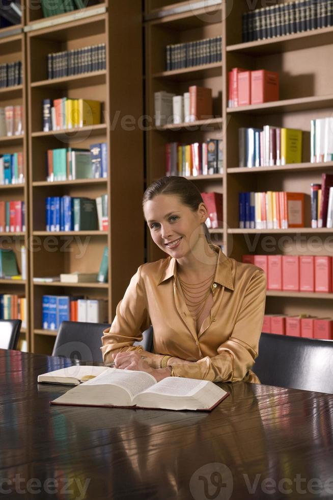 Frau mit Buch am Schreibtisch in der Bibliothek foto