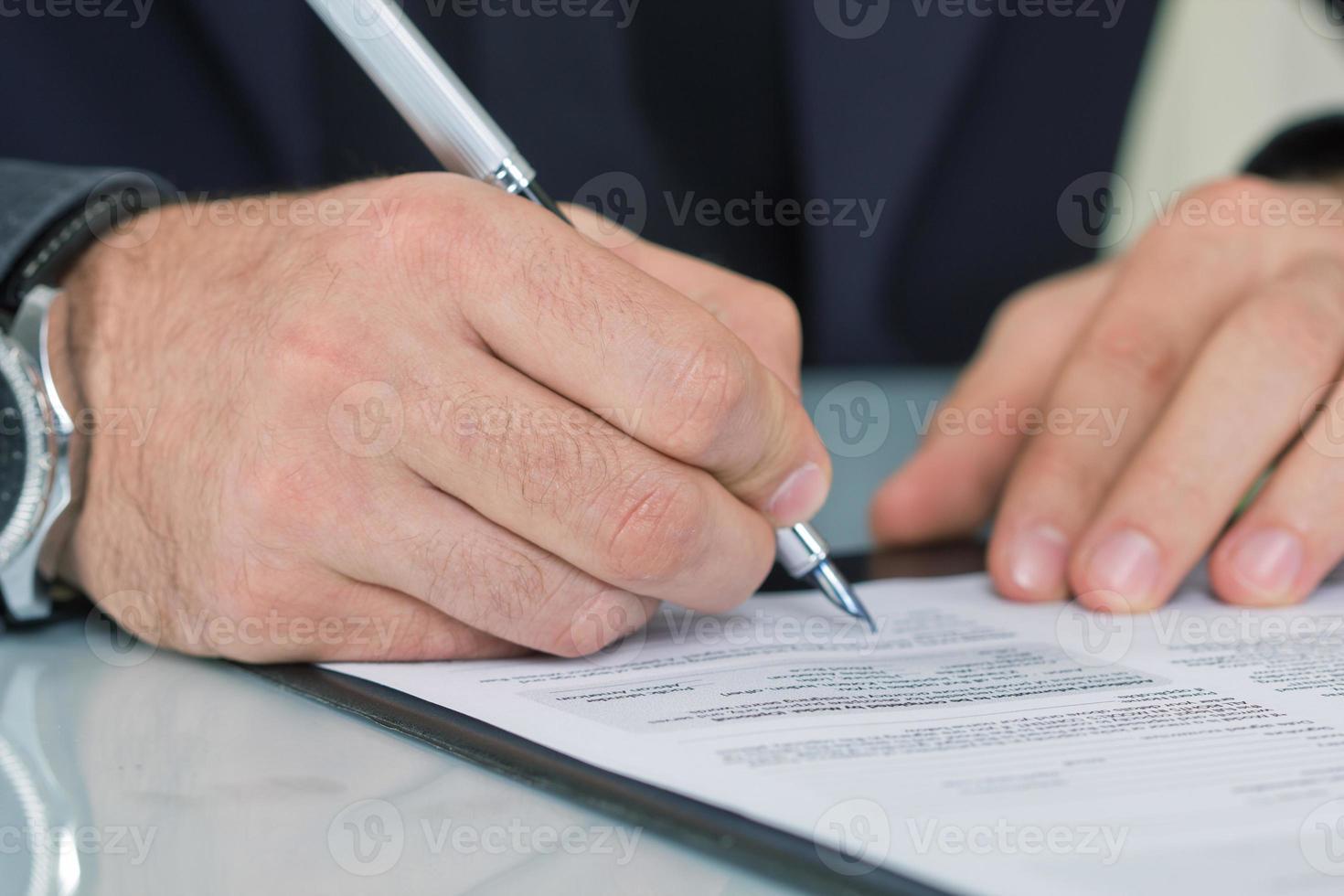 Geschäftsmann, der am Schreibtisch sitzt und einen Vertrag unterschreibt foto