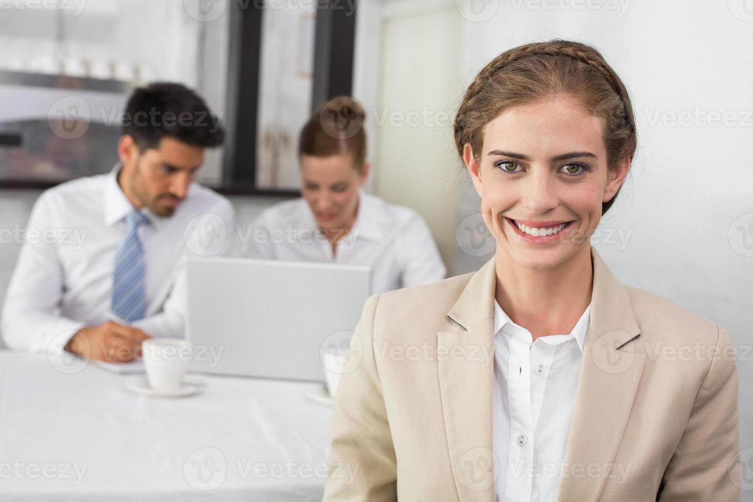 lächelnde Geschäftsfrau mit Kollegen am Schreibtisch foto