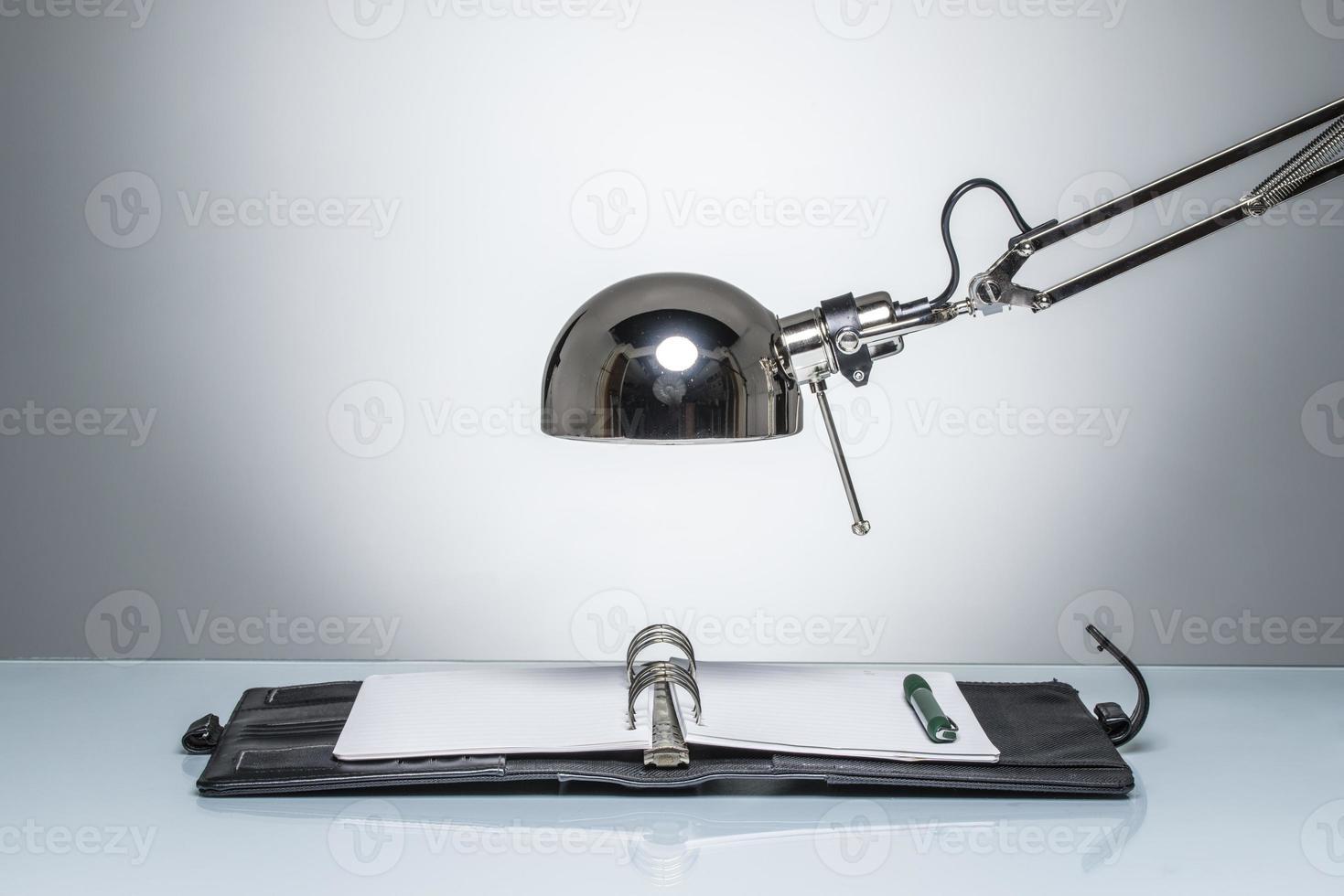 Aufleuchten des Notizbuch-Tagebuchschreibens mit Schreibtischlampe foto