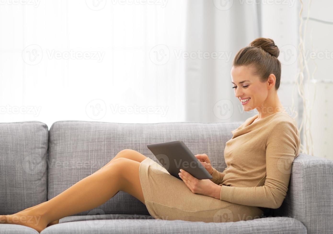 junge Frau, die auf Sofa sitzt und Tablet-PC verwendet foto