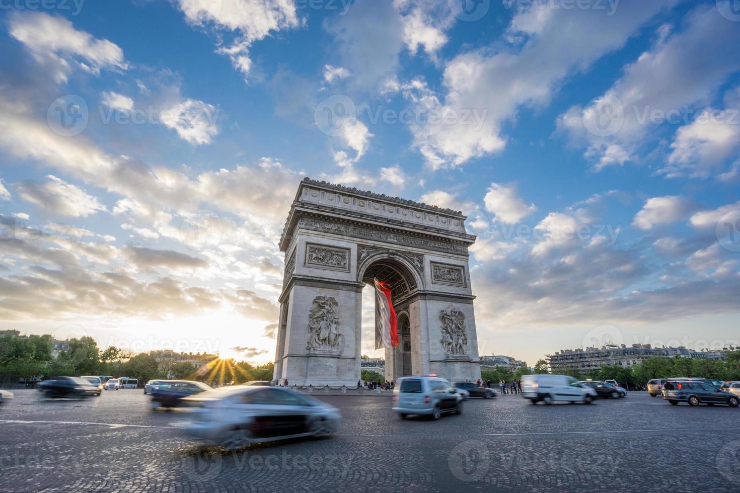 Arc de Triomphe und verschwommener Verkehr bei Sonnenuntergang foto
