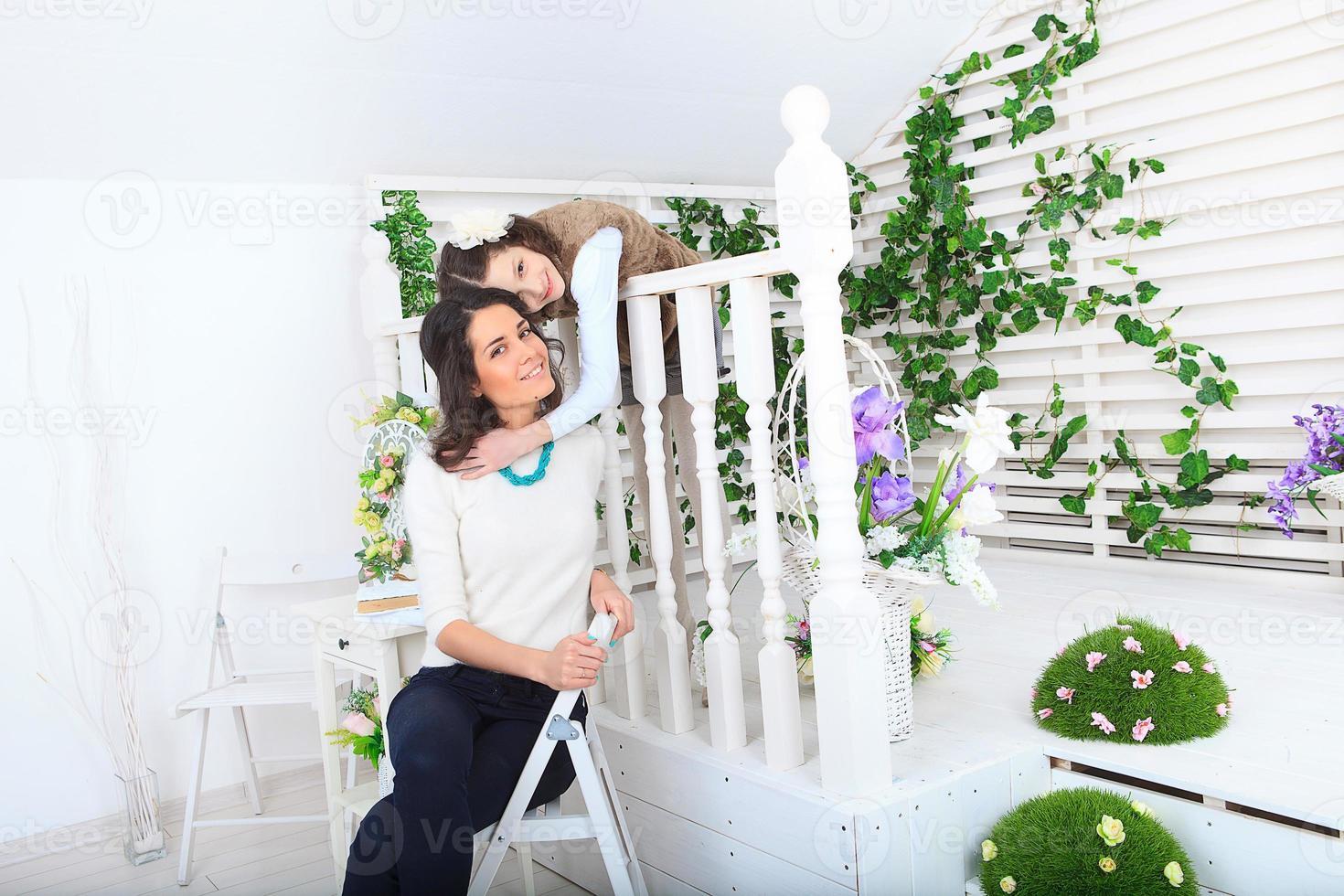 schöne junge Mutter, die als ihre Tochter lächelt foto