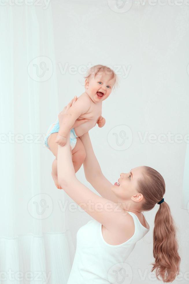Mutter spielt mit ihrem Kind und kotzt das Baby foto