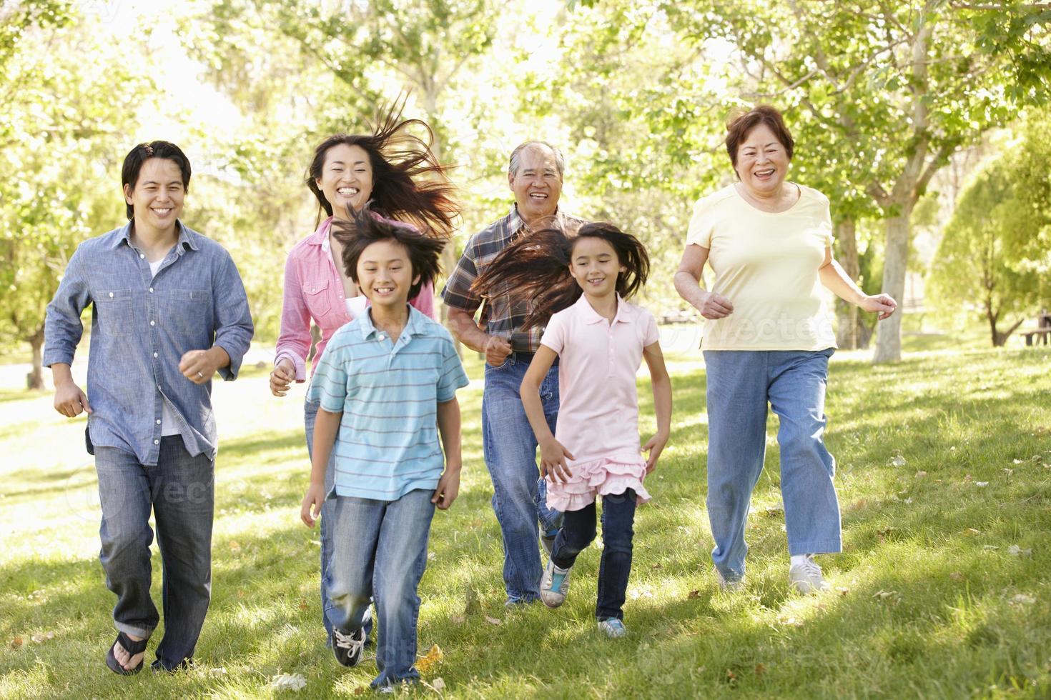 asiatische Familie mit mehreren Generationen, die im Park läuft foto