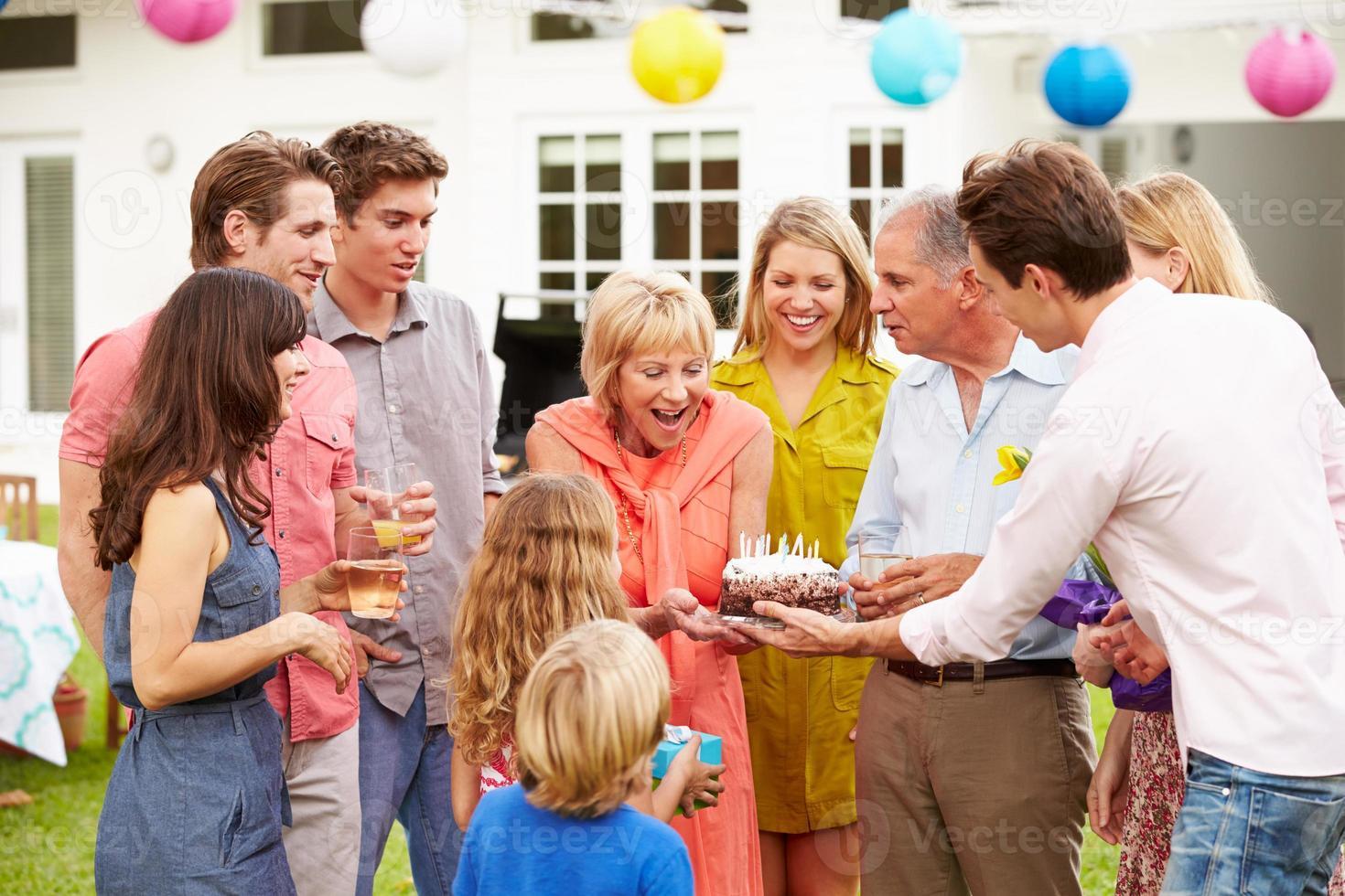 Familie mit mehreren Generationen, die Geburtstag im Garten feiert foto