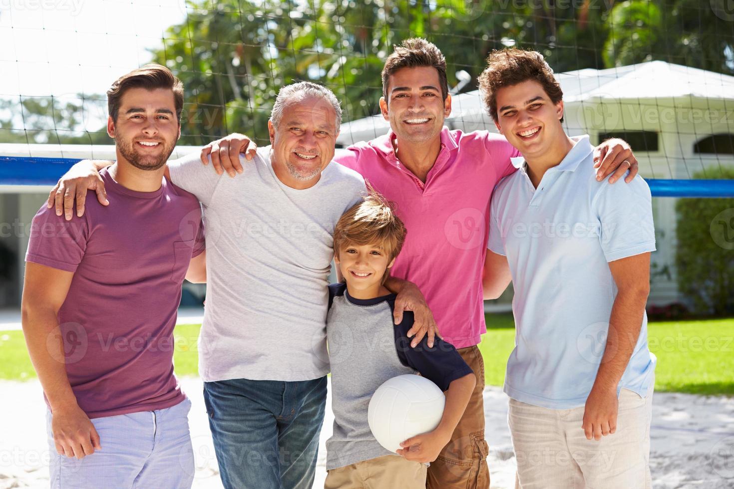 männliche Mehrgenerationenfamilie, die Volleyball im Garten spielt foto