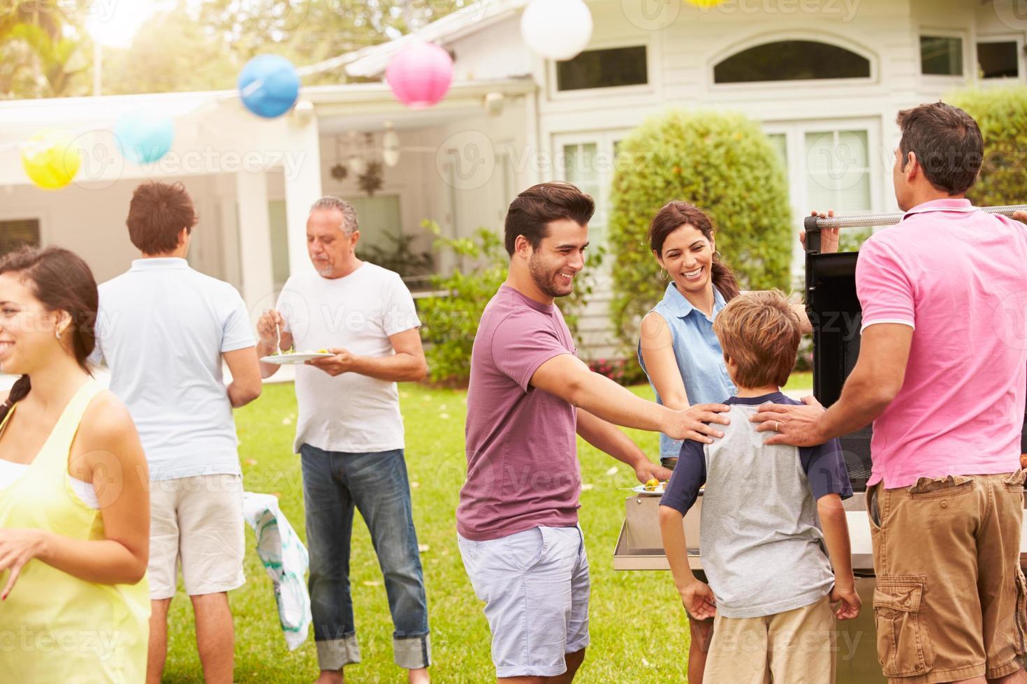 Familie mit mehreren Generationen, die gemeinsam im Garten feiern foto