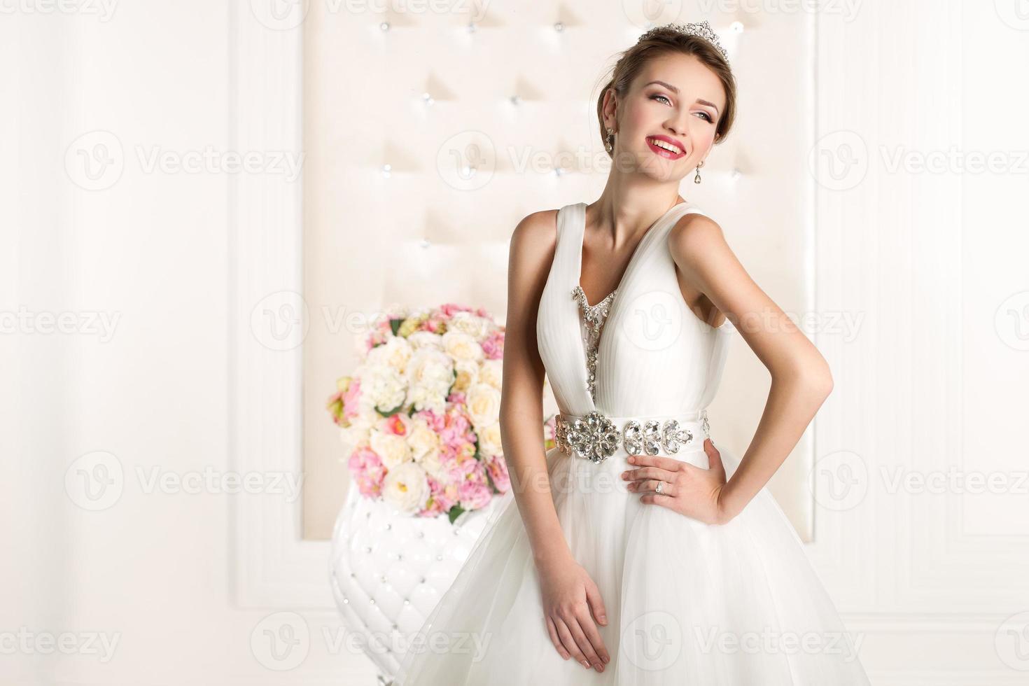 wunderschöne Braut mit weißem Kleid mit Blumenstrauß foto