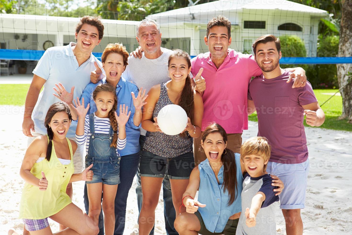 Mehrgenerationenfamilie, die Volleyball im Garten spielt foto