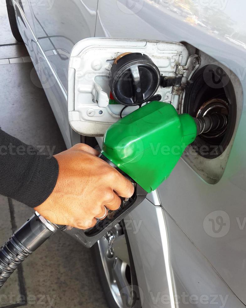 Nahaufnahme des Mannes, der Benzinkraftstoff im Auto pumpt foto