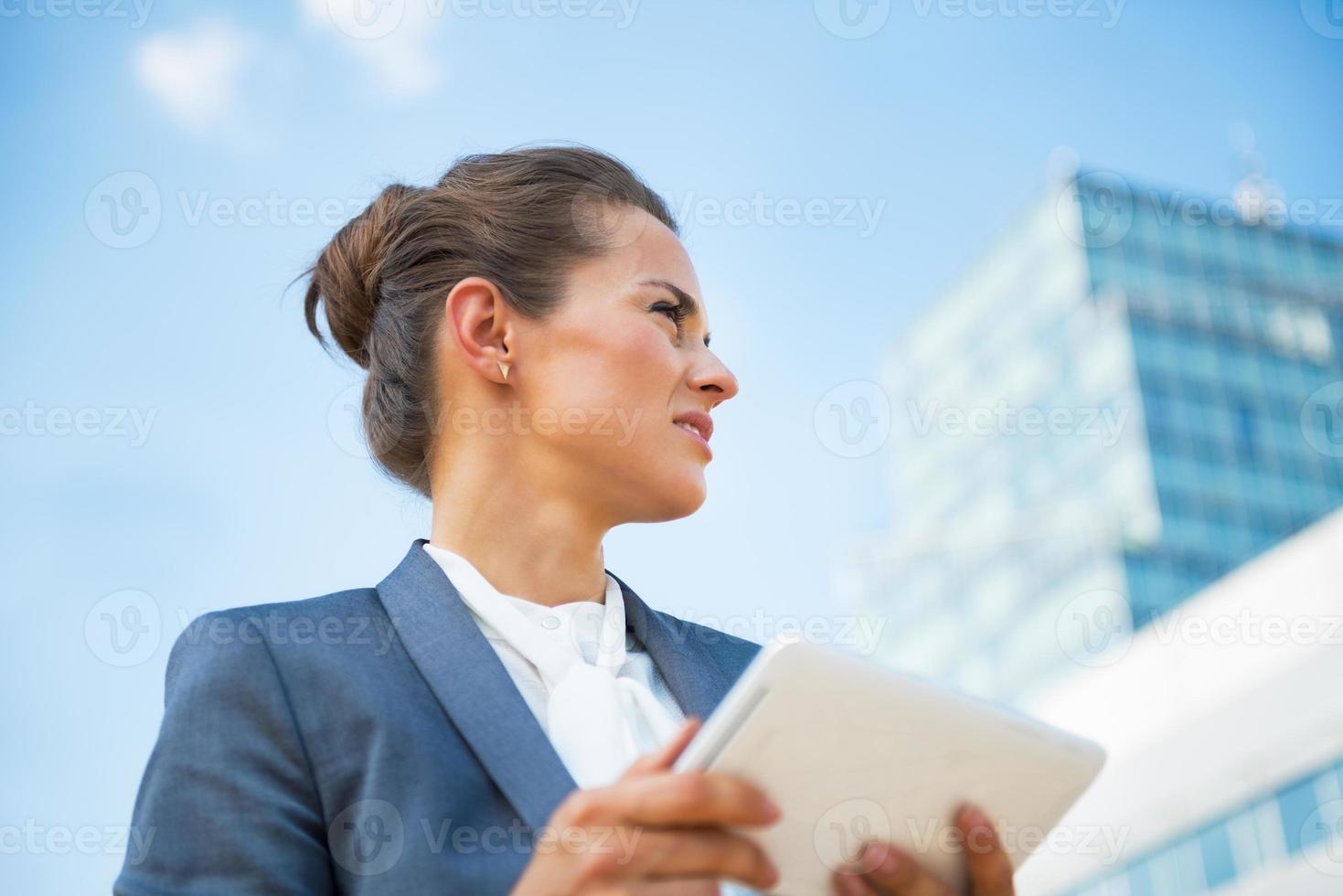 Geschäftsfrau mit Tablet-PC vor Bürogebäude foto