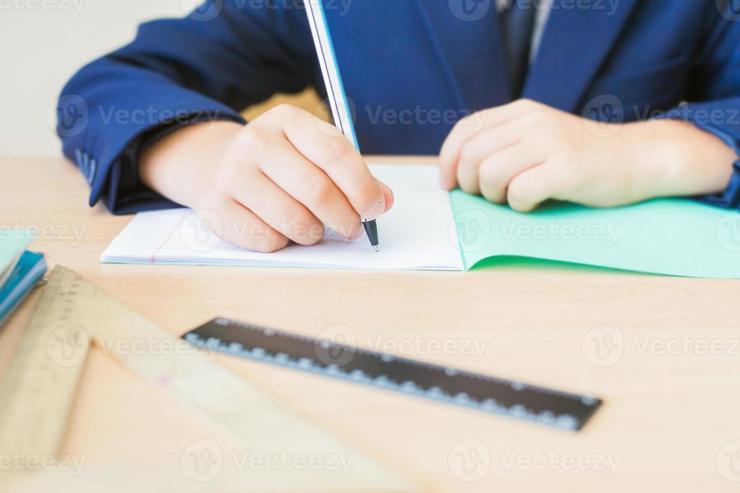Desktop-Hintergrund des Studenten, der am Schreibtisch für Klassenarbeit sitzt foto