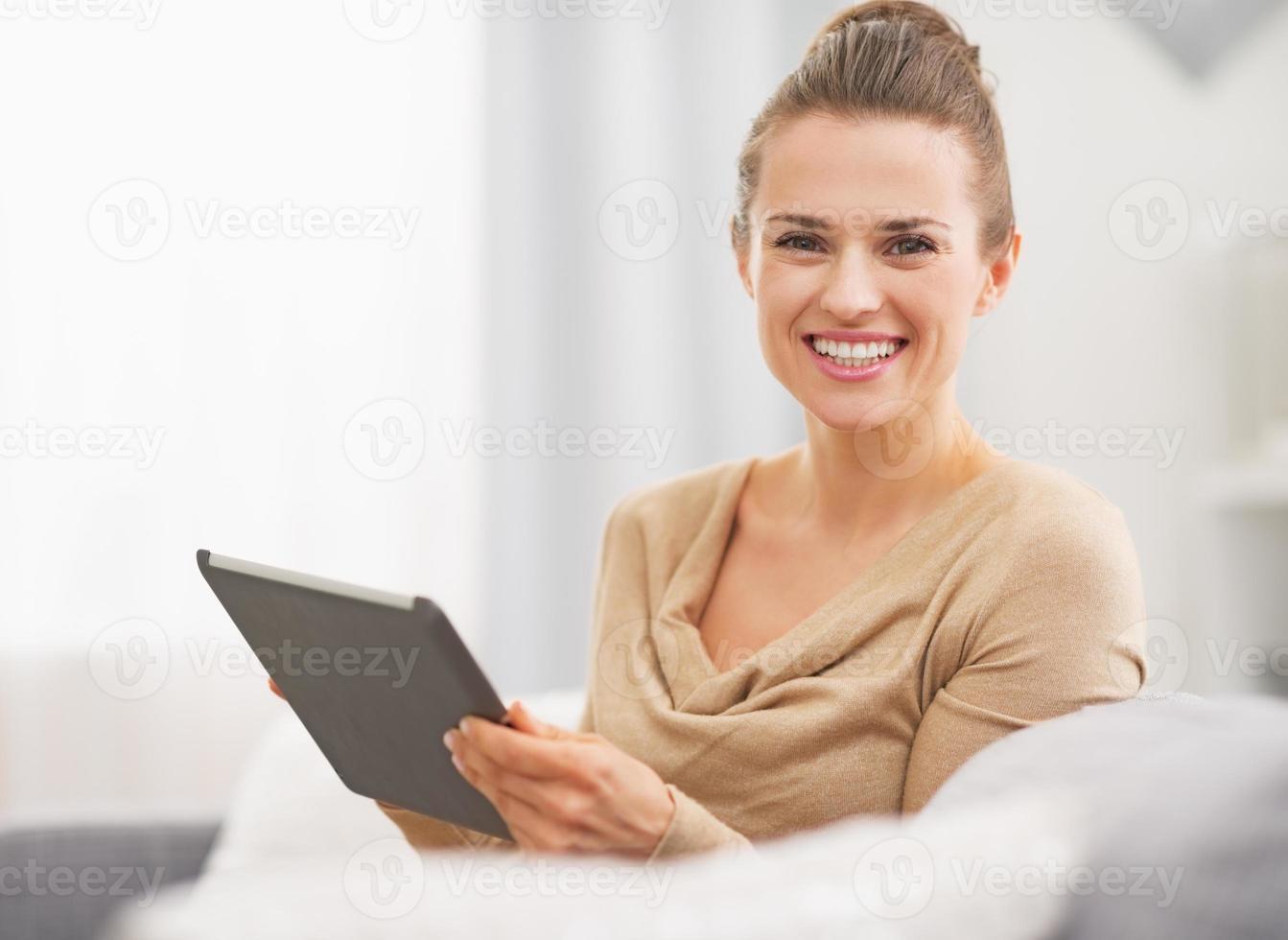 lächelnde junge Frau, die auf Sofa sitzt und Tablet-PC verwendet foto