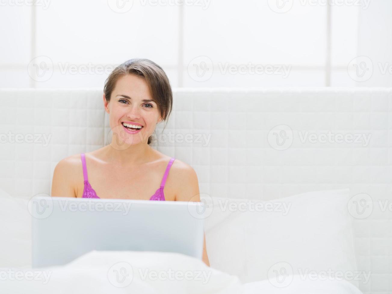 glückliche junge Frau, die am Laptop arbeitet foto