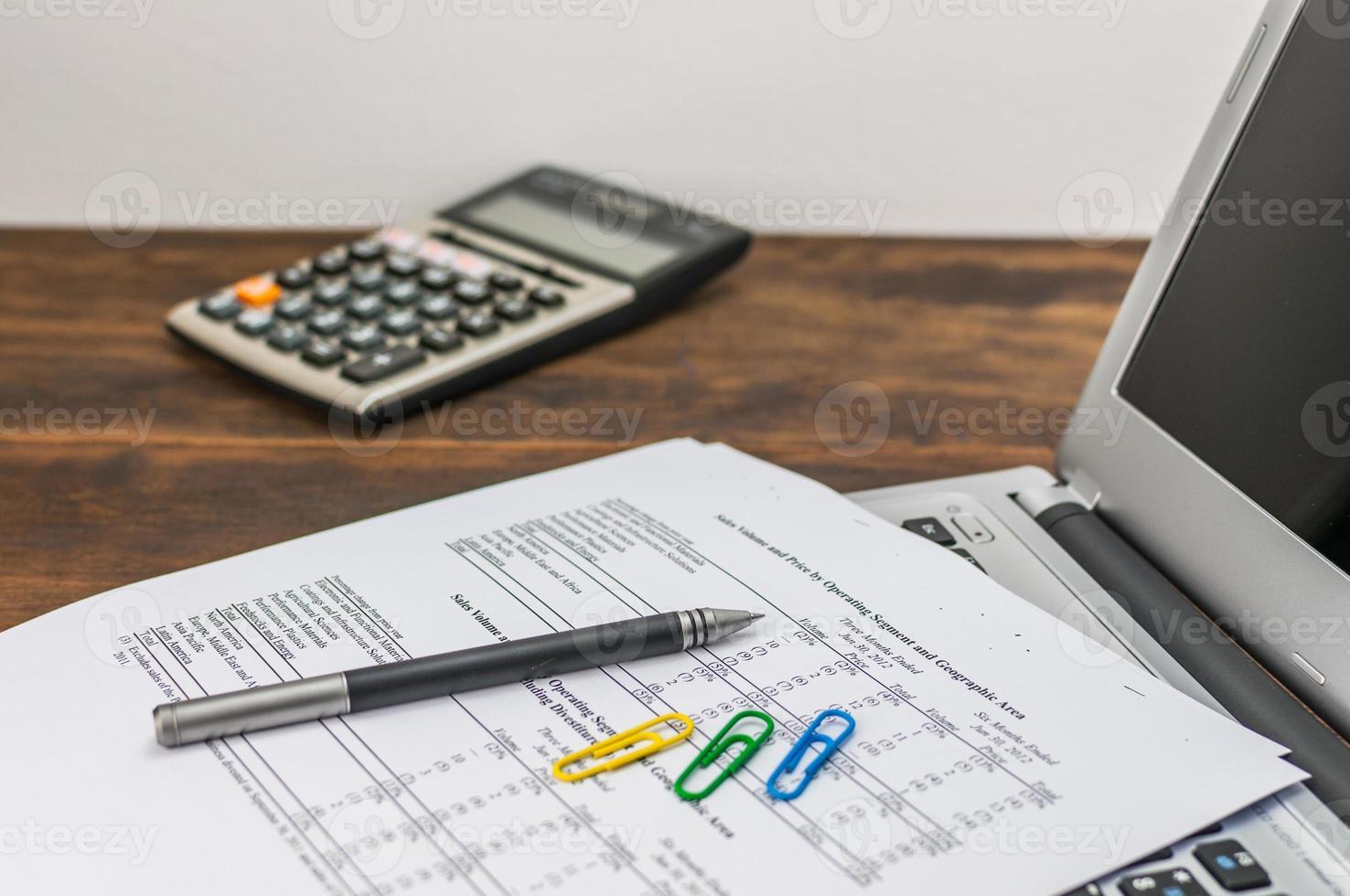 Dokument, Stift und Clips über Laptop mit Caculator foto