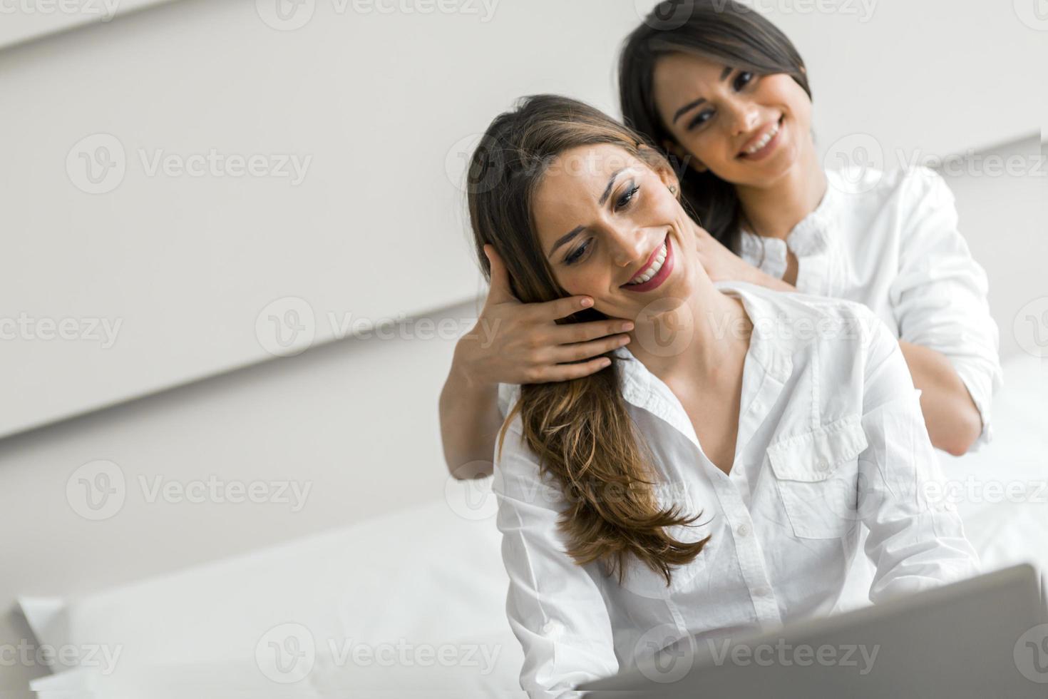 zwei schöne Frauen, die im Bett ein Notizbuch benutzen foto