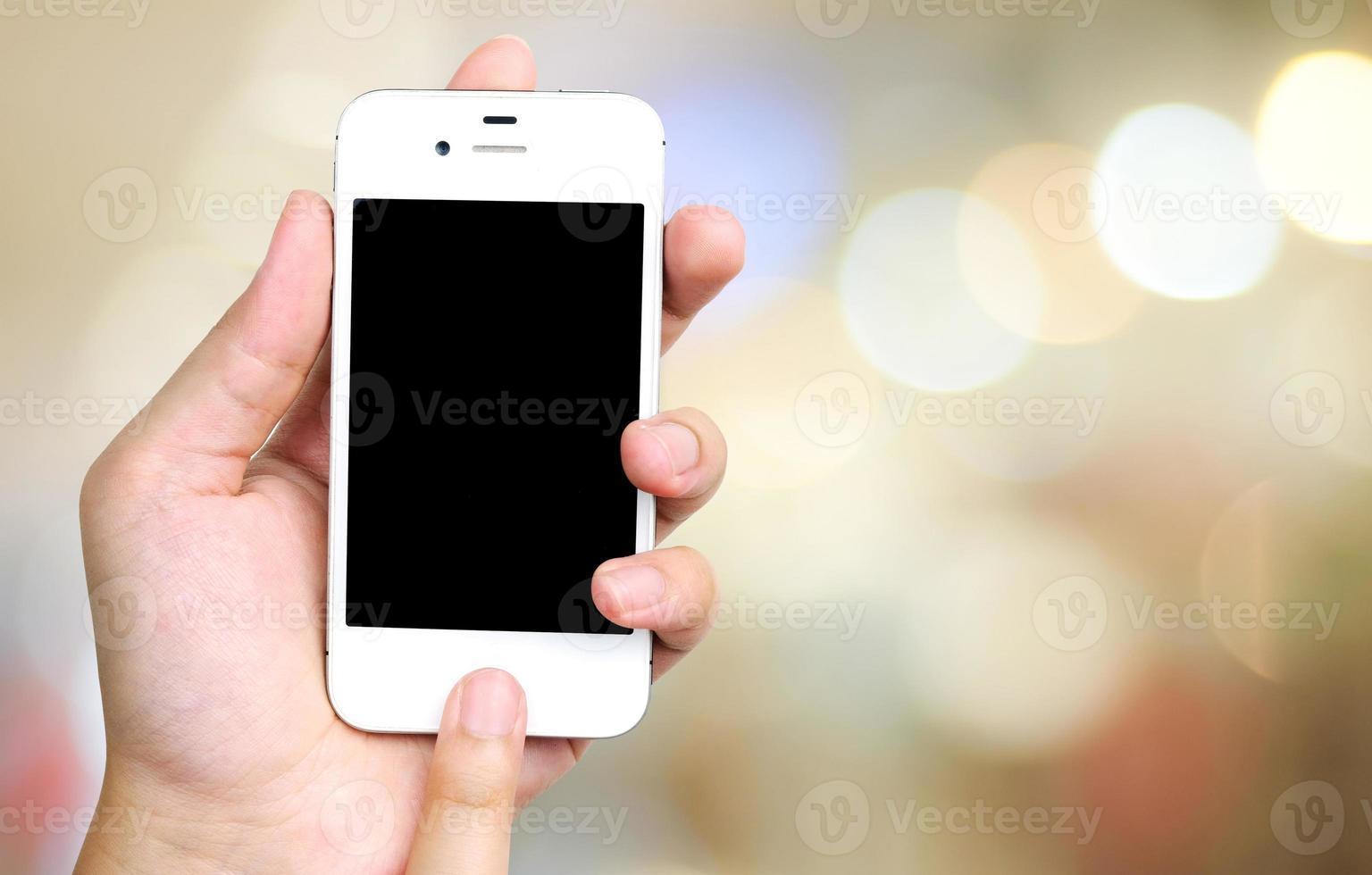 Smartphone in der Hand auf Bokeh Hintergrund foto