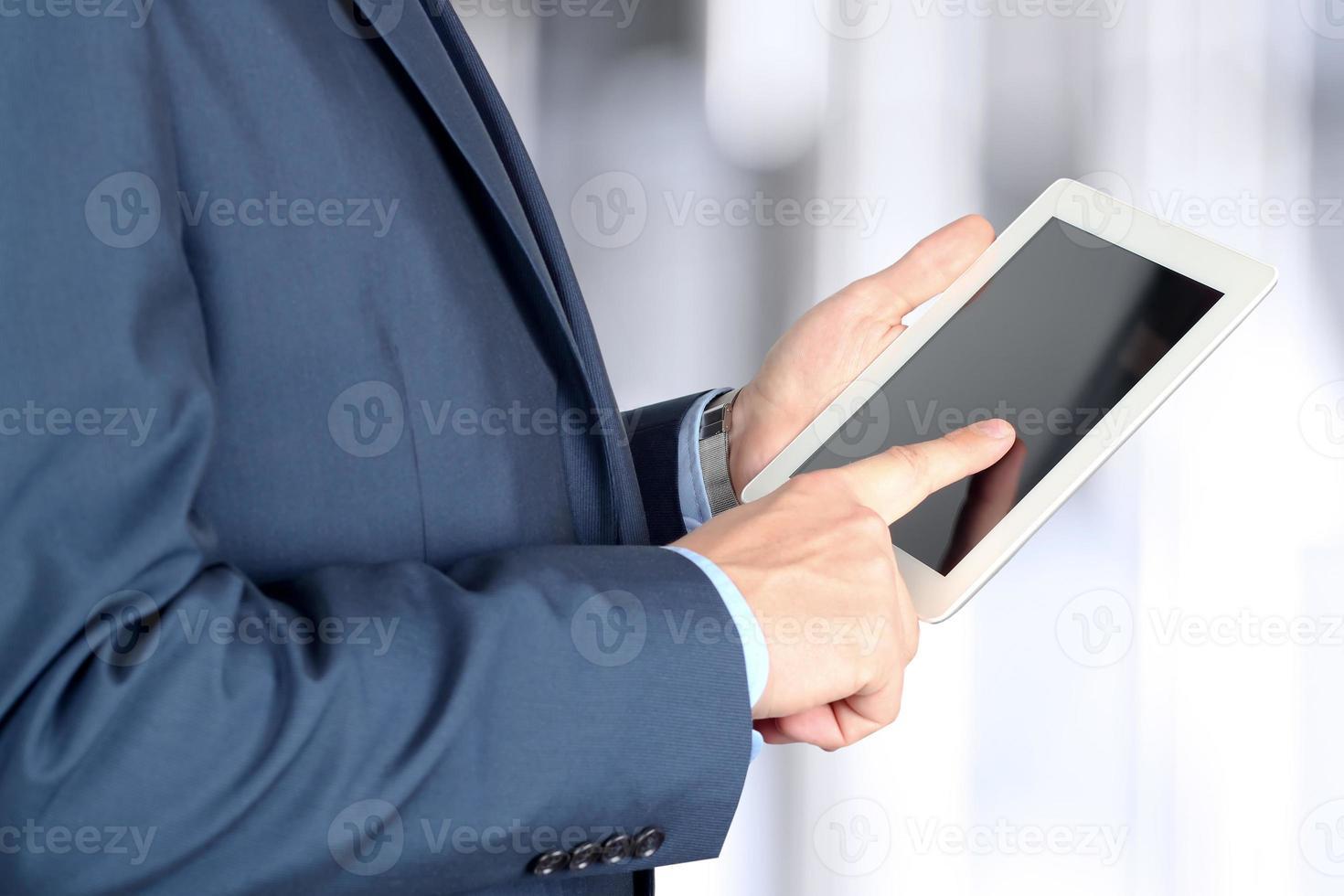 junger Geschäftsmann, der an einem digitalen Tablett arbeitet foto
