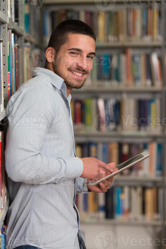 glücklicher männlicher Student, der mit Laptop in Bibliothek arbeitet foto