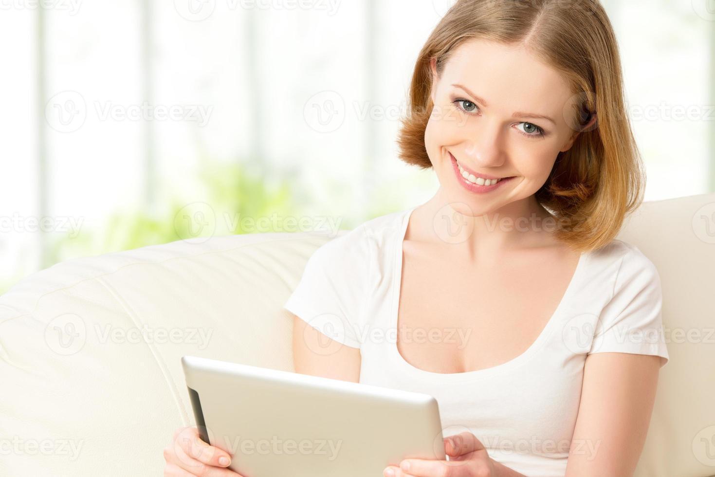 glückliche frau mit tablet pc zu hause foto