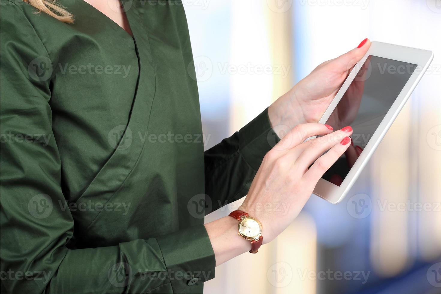 Geschäftsfrau hält und arbeitet mit einem digitalen Tablet foto