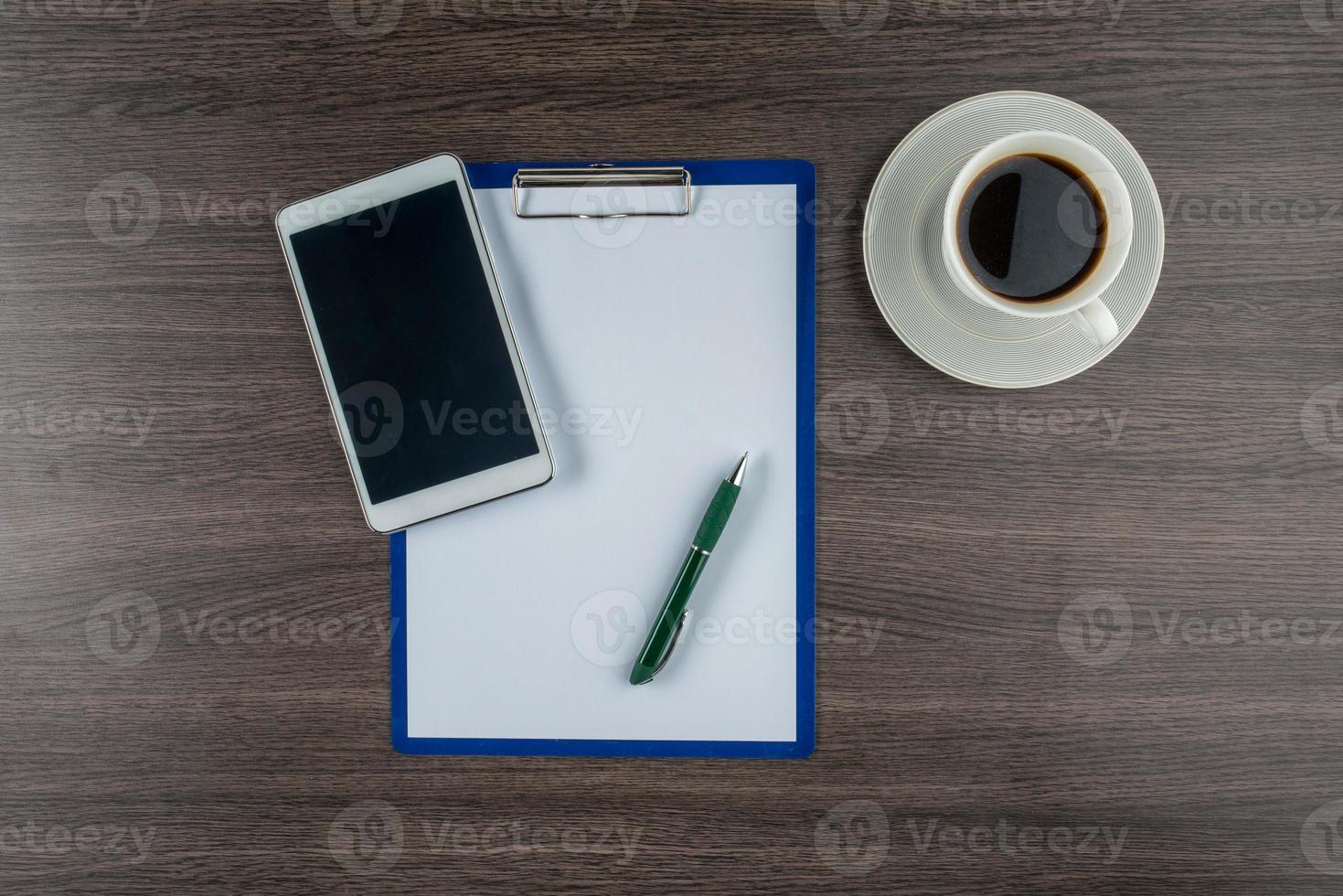 Tablette, Papier und Stift mit einer Tasse Kaffee foto