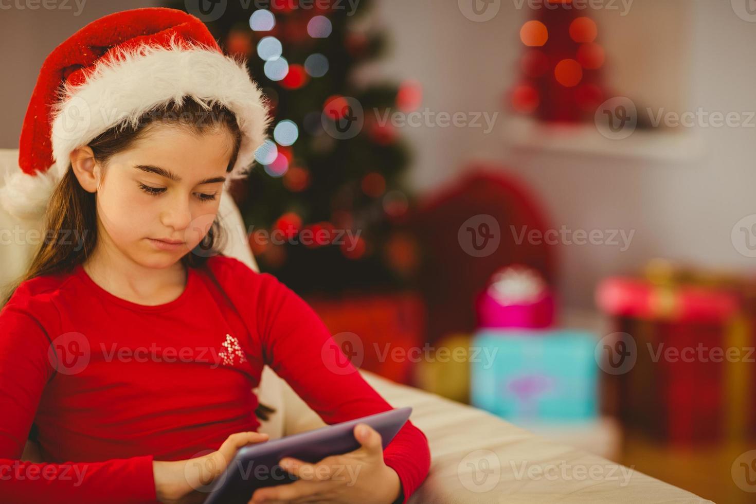 festliches kleines Mädchen mit Tablet-PC auf der Couch foto