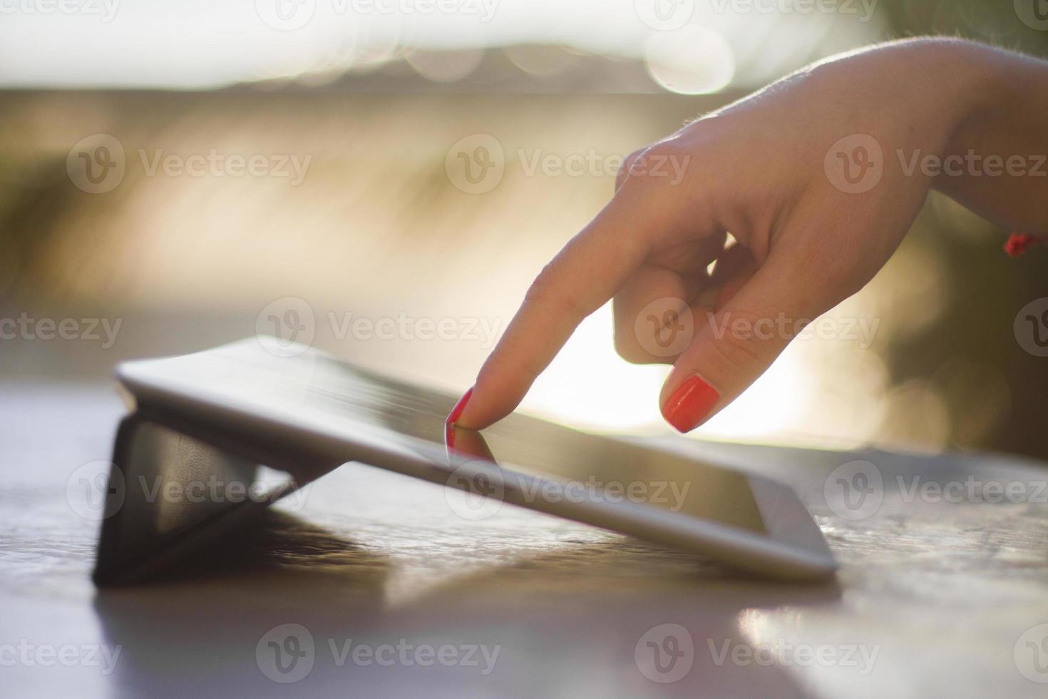 Frauenhand, die auf ein digitales Tablett drückt foto