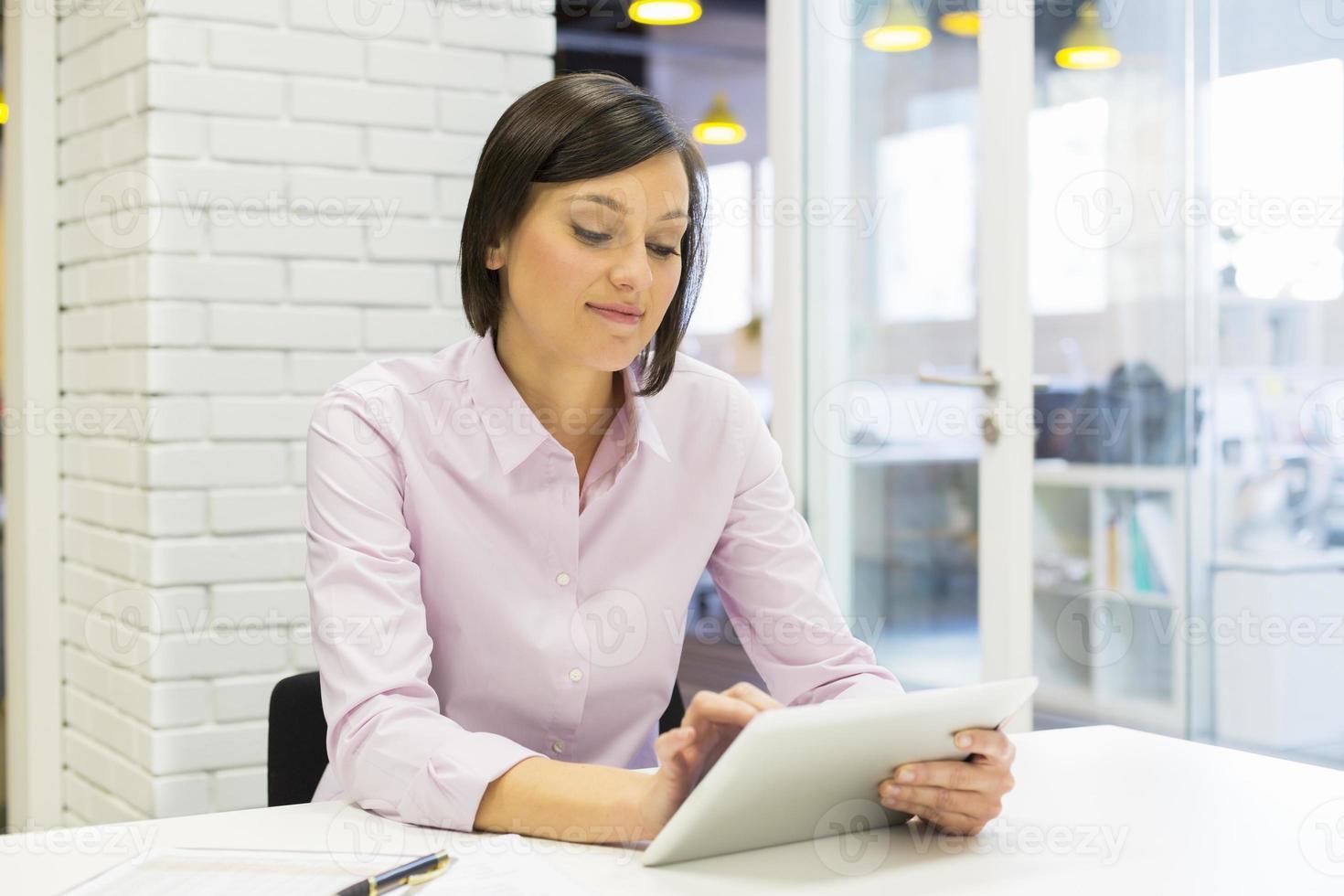 hübsche Geschäftsfrau, die auf digitalem Tablett im Büro arbeitet foto