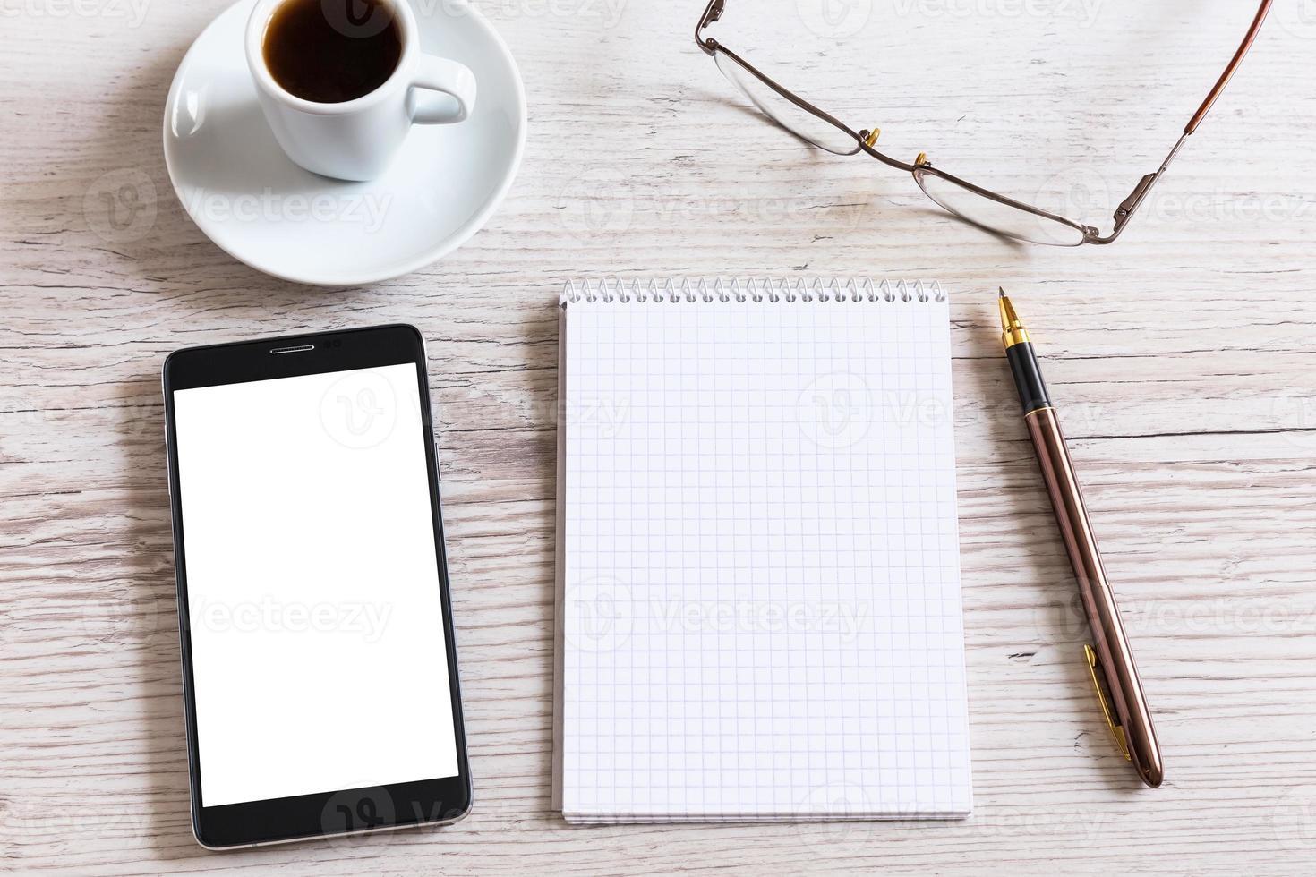 Notizbuch mit Stift, Smartphone und Kaffeetasse foto