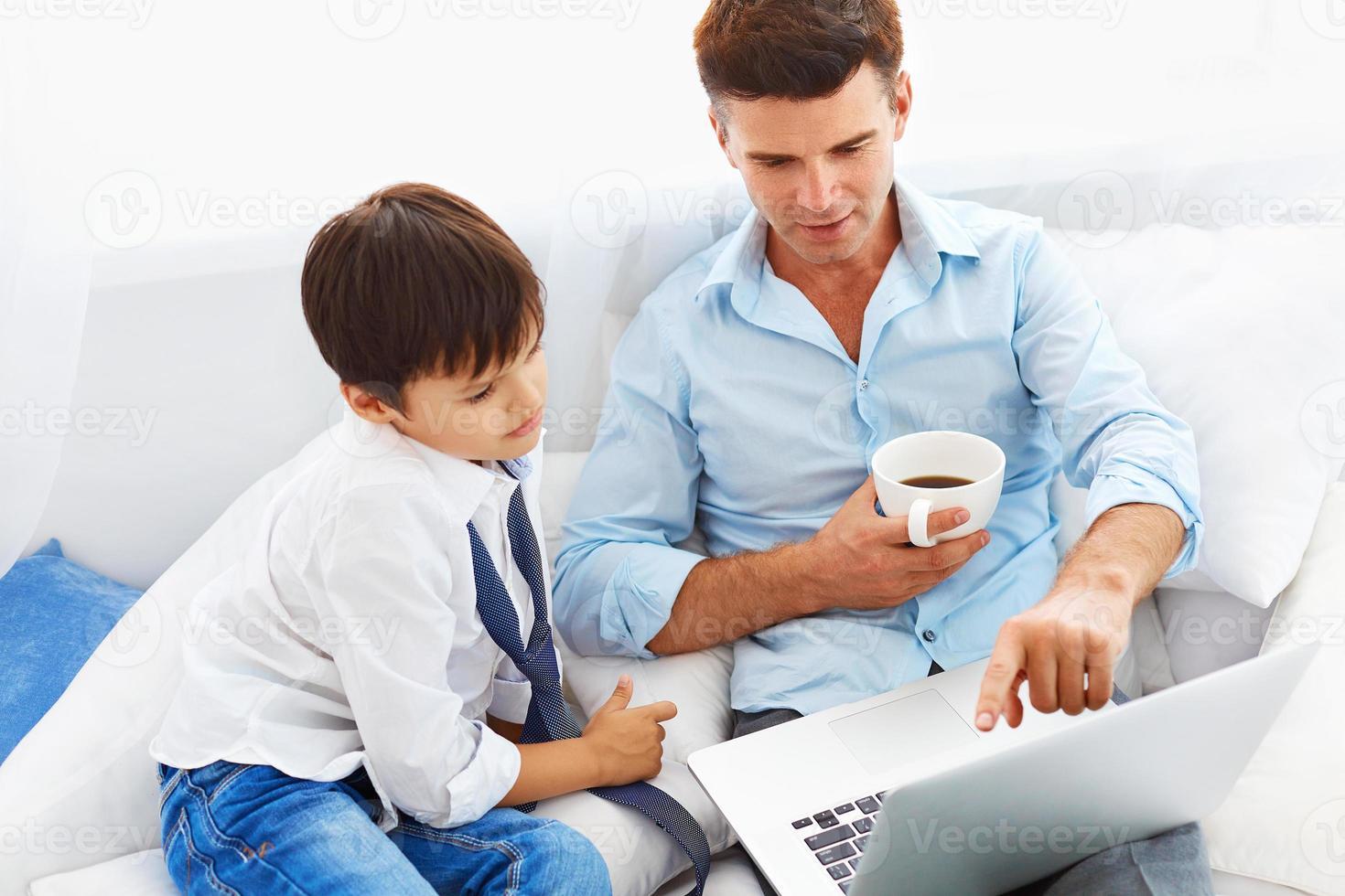 Vater trinkt Kaffee und bringt Sohn bei, wie man ein Notizbuch benutzt. foto