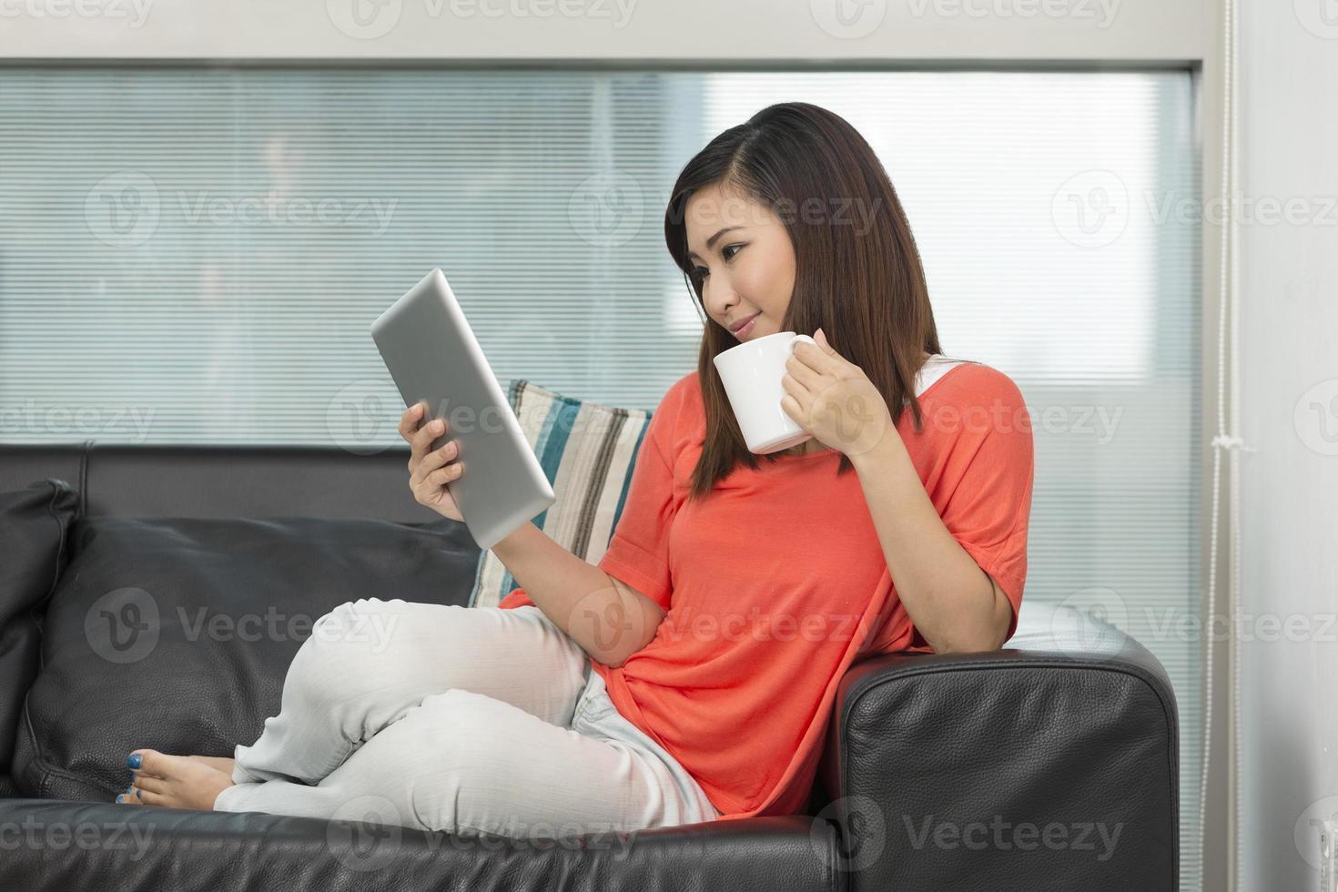 asiatische Frau zu Hause beim Lesen eines Tablet-PCs. foto
