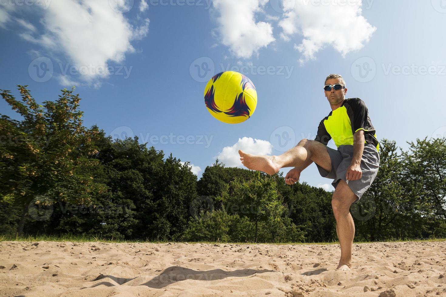 Beach-Soccer-Spieler in einem Kick foto