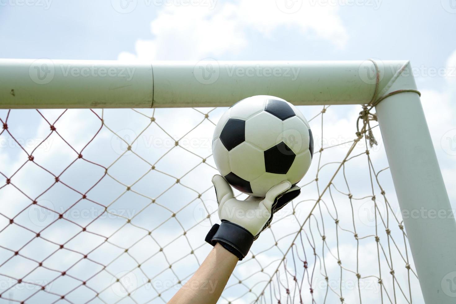 Der Torhüter fing den Ball mit den Händen foto