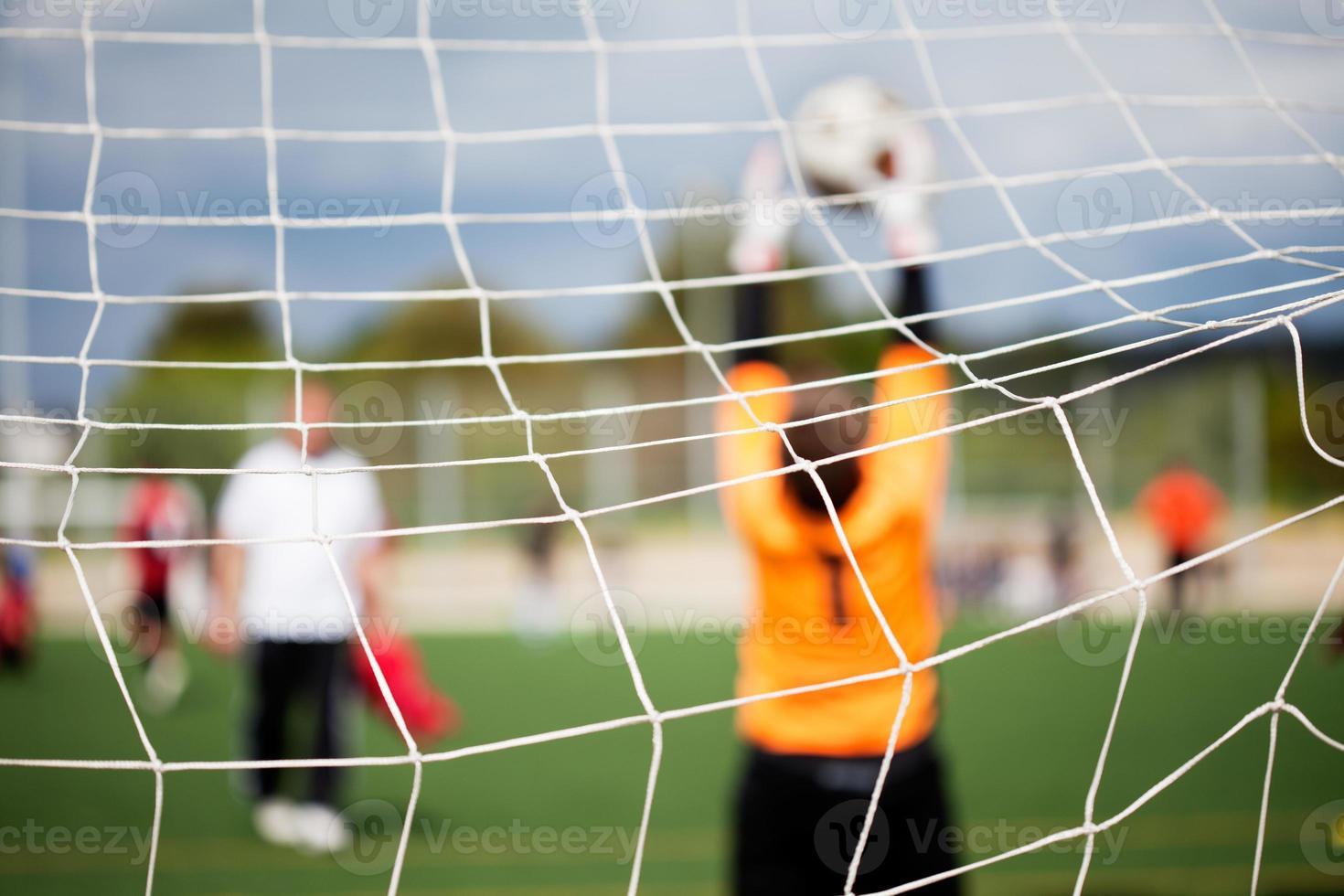 Ein Fußballspiel mit dem Netz im Fokus, wenn ein Torwart den Ball stoppt foto