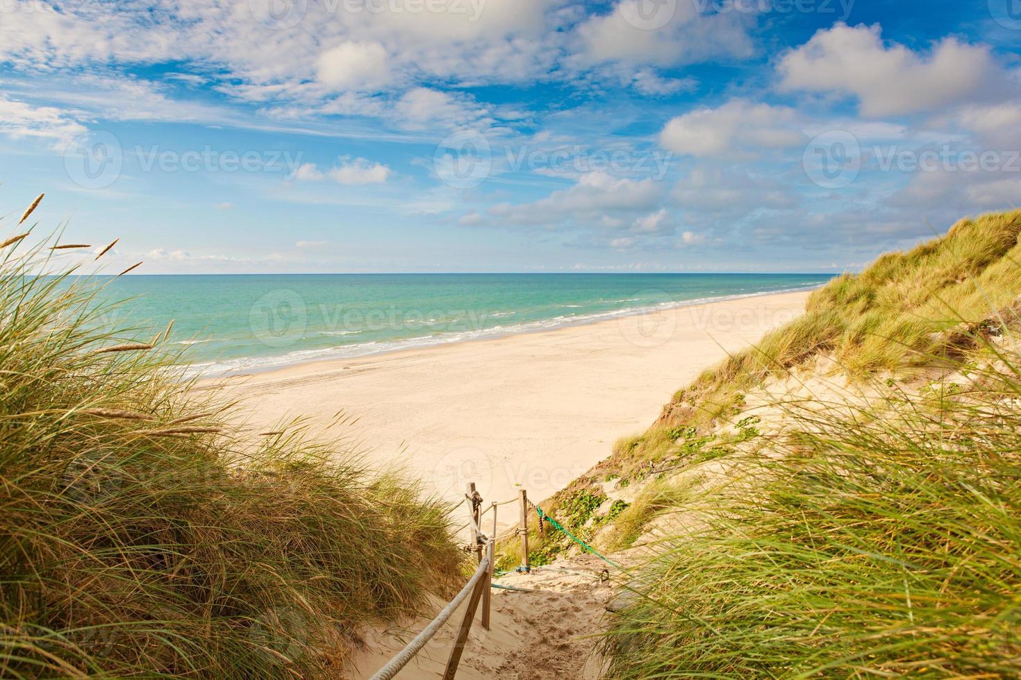 Meer mit Sanddünen und buntem Himmel foto