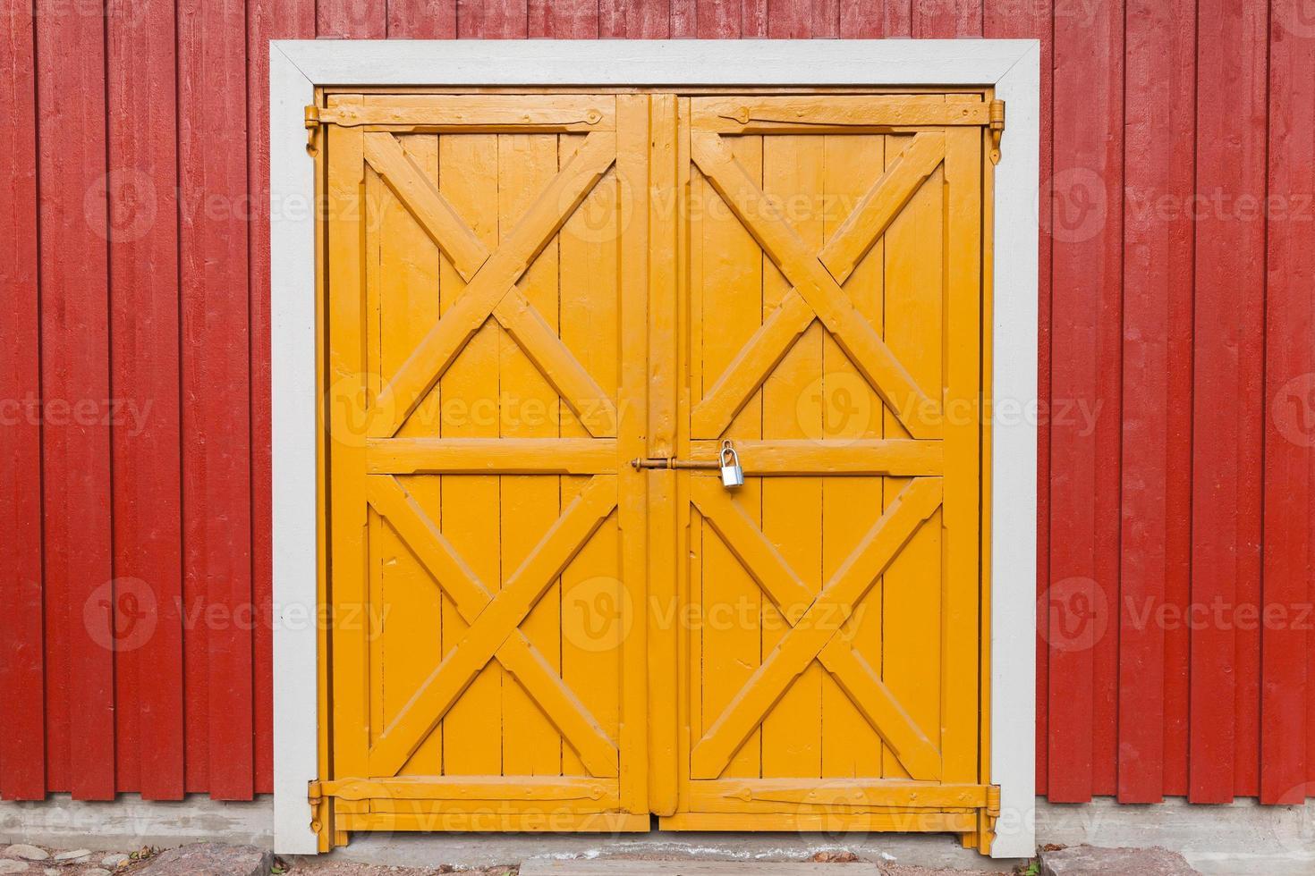 verschlossenes gelbes Holztor in der roten Wand, Hintergrund foto