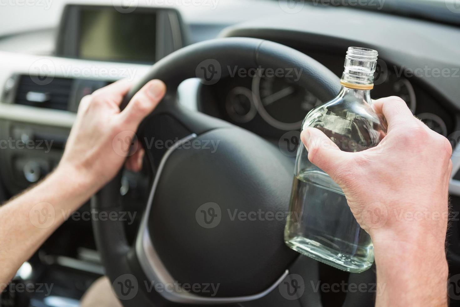 Nahaufnahme des Fahrers, der Wodka hält foto