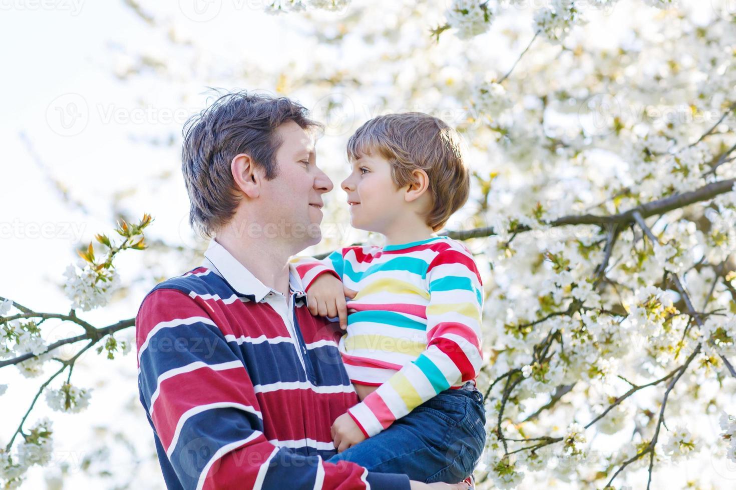 junger Vater und kleiner Junge im blühenden Garten foto