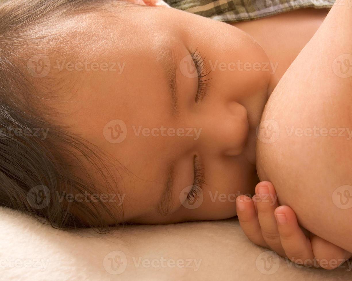 schläfriger Junge, der das Stillen genießt foto